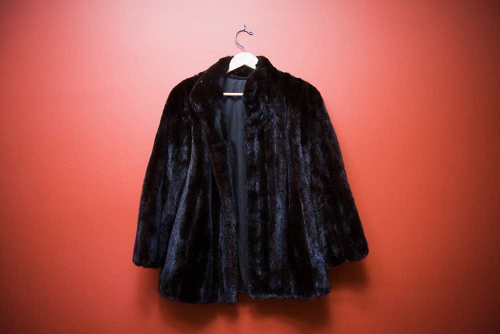 A woman's black diamond mink fur coat (jacket) hangs from a hook against a red wall in a home in Seattle, Washington.