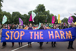 London, UK. 26th August, 2021. Environmental activists from Extinction Rebellion take part in a Stop The Harm march during the fourth day of Impossible Rebellion protests. Extinction Rebellion are calling on the UK government to cease all new fossil fuel investment with immediate effect.