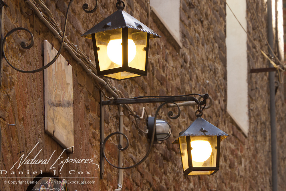Lamps hang in above the streets of Siena, Italy
