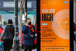 © Licensed to London News Pictures. 26/10/2020. London, UK. A woman wearing a face covering walks past a COVID-19 high alert level sign in north London. It has been reported that the government is planning for an extra tougher fourth tier of Covid-19 restrictions in England if coronavirus cases increase in the coming weeks. The measures could see restaurants, pubs and non-essential businesses such as clothes shops forced to close in areas where tier 3 rules have not brought the virus under control. Currently all 32 boroughs plus the City of London are in tier two, where there is a high risk of coronavirus. Photo credit: Dinendra Haria/LNP
