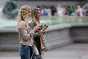 Young women walk cross Trafalgar Square while using their mobile phones, on 20th May 2019, in London, England.