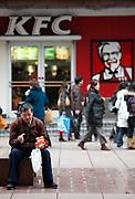 A man has a snack out side of a KFC store in Shanghai, China on 04 February, 2009.  Yum Brands Inc, the parent of KFC, Taco Bell, and Pizza Hut, is the largest foreign fast food store chain in China, almost double the size of its nearest competitor McDonald's.