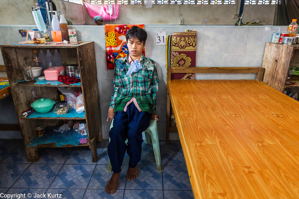 05 MARCH 2014 - MAE SOT, TAK, THAILAND: A boy waits for his family to join him at his bed side in the Mae Tao Clinic in Mae Sot. The Mae Tao Clinic provides  healthcare to over 150,000 displaced Burmese per year and is the leading healthcare provider for Burmese along the Thai-Myanmar border. Reforms in Myanmar have alllowed NGOs to operate in Myanmar, as a result many NGOs are shifting resources to operations to Myanmar, leaving Burmese migrants and refugees in Thailand vulnerable.     PHOTO BY JACK KURTZ