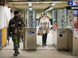© Licensed to London News Pictures. 25/11/2015. Brussels, Belgium. An armed member of the Belgian walks past a commuter at Louise Metro station in Central Brussels where the Metro transport system is now running and some schools have reopened following closure due to security fears. The Belgian capital has been on lockdown and the highest security alert due to fears of a terrorist attack following the recent attacks in Paris. Photo credit: Ben Cawthra/LNP