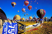 Envelope being rolled out with hot air balloons rising in the background at the International Balloon Fiesta, Albuquerque, New Mexico