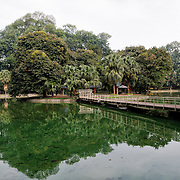 A bridge connects a small island in the middle of a lake at the Hanoi Botanical Gardens (Vuon Bach Thao).
