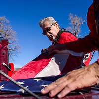 Lionel Gutierrez and other members of Veterans Helping Veterans fold old flags to prepare them for a ceremonial retiring Friday in Thoreau.