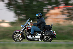 A man rides his red and black motorcycle down a highway