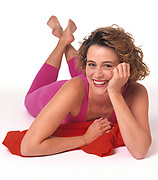 Happy exercise woman laying on white seamless paper floor wearing pink exercise clothes. Magenta leotard and tights resting on red sweatshirt