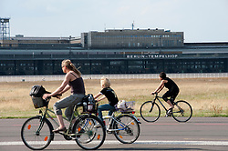 People cycling on runway at new city public Tempelhofer Park on site of famous former Tempelhof Airport in Berlin Germany
