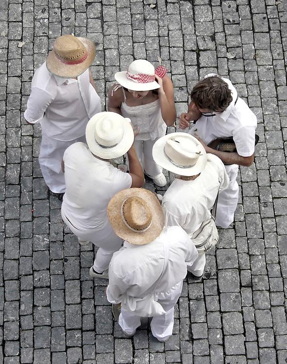 ESP, Spanien, Kanarische Inseln,  La Palma , Santa Cruz de La Palma, 27.02.2006: -  Am Rosenmontag in der Hauptstadt Santa Cruz in der Fussgangerzone der Calle O'Daly  steht eine Gruppe traditionell weiss gekleideter Personen. Symbolisch verspottet werden die Los Indianos, die einstigen Auswanderer nach Kuba und Lateinamerika, die versuchten ihr Glueck zu machen, und spaeter teilweise betucht , in ihrer kolonialen weissen Kleidung nach La Palma zurueck kehrten. Beim Umzug durch die Strassen von Santa Cruz wirft jeder mit weissem Talg-Puder um sich. Besonders trifft es diejenigen die nicht weiss gekleidet sind.  Foto: Frank-Udo Tielmann,  | ESP, Spain, Canarian Islands,  La Palma , Santa Cruz de La Palma, 2006.02.27. : - A group of Los Indianos stands in the Calle O'Daly usually the main shopping sreet in the capital Santa Cruz de La Palma on Monday before lent.  Traditionally everybody wears white clothes on that day symbolizing the return of the Los Indianos, Palmeros who tried to make a better life in Cuba or latin america. Later they came back as ostentatious rich people.  Everybody throws white talcum powder esp. towards those who do not wear white clothes.   Photo by Frank-Udo Tielmann, |.