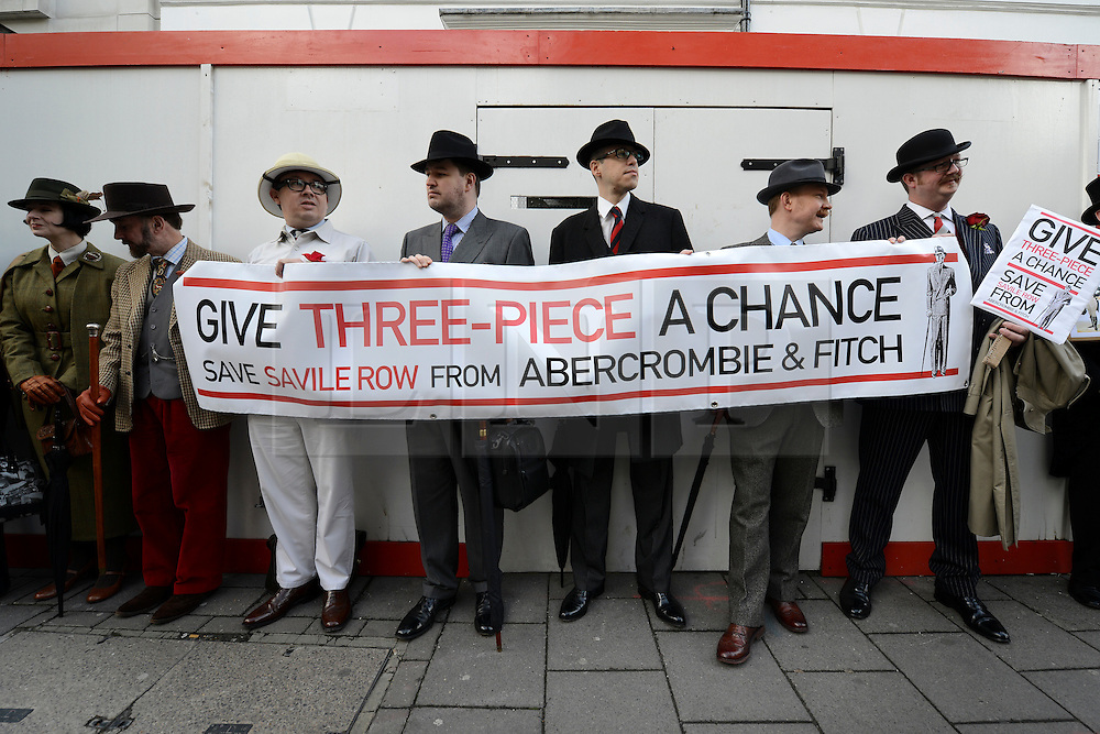 © Licensed to London News Pictures. 23/04/2012. London, UK . People with a banner outside the proposed site. A protest organised today, 23rd April 2012, by Chap Magazine and the Tailors of Savile Row to petition against the proposed opening of a new Abercrombie and Fitch Store on Savile Row. The protesters gathered to sing 'Give 3 Piece A Chance' outside the present store on Burlington Gardens. Photo credit : Stephen Simpson/LNP