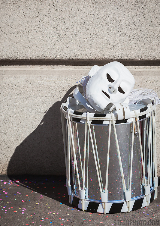 A mask and drum resting on the ground while musicians take a break during Carnival (Fastnacht) in Basel, Switzerland.