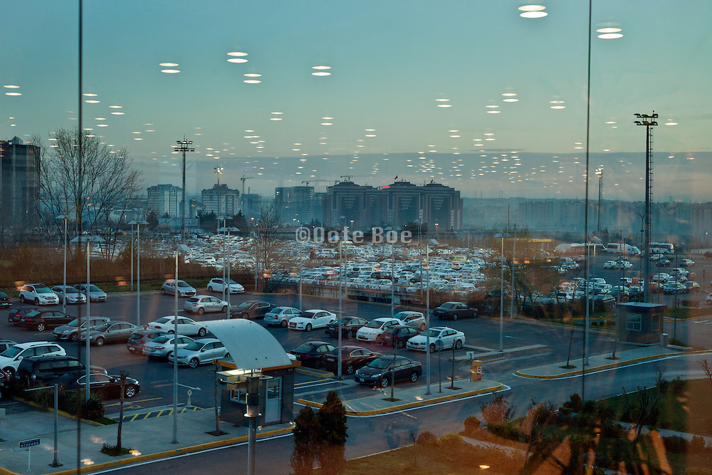 hall lights reflecting in window with outside a large car parking at Ataturk airport Istanbul Turkey at sunrise