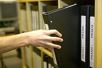 young student researching in the local records office, Lancashire pulling a book from the shelf