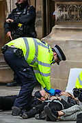 Police handcuff an Extinction Rebellion activist who glued themselves in front of the Peers Gate, outside Westminster Palace of the Houses of Parliament on Thursday, Sept 3, 2020. Environmental non-violent activists group Extinction Rebellion enters its 3rd day of continuous ten days to disrupt political institutions throughout peaceful actions swarming central London into a standoff, demanding that central government obeys and delivers Climate Emergency bill.