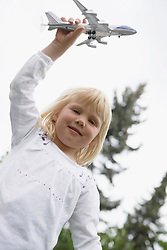 Small blonde girl playing with toy airplane