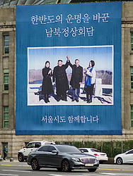 October 9, 2018 - Seoul, Gyeonggi, South Korea - Traffic on Sejong-Daero Street goes past a large sign hanging from the Seoul public library marking the September summit meeting between North Korean lead Kim Jong-un (center left) and his wife, Ri Sol-ju (left) and South Korean President Moon Jae-in (center right) and his wife,  Kim Jung-sook. (Credit Image: © Jack Kurtz/ZUMA Wire)