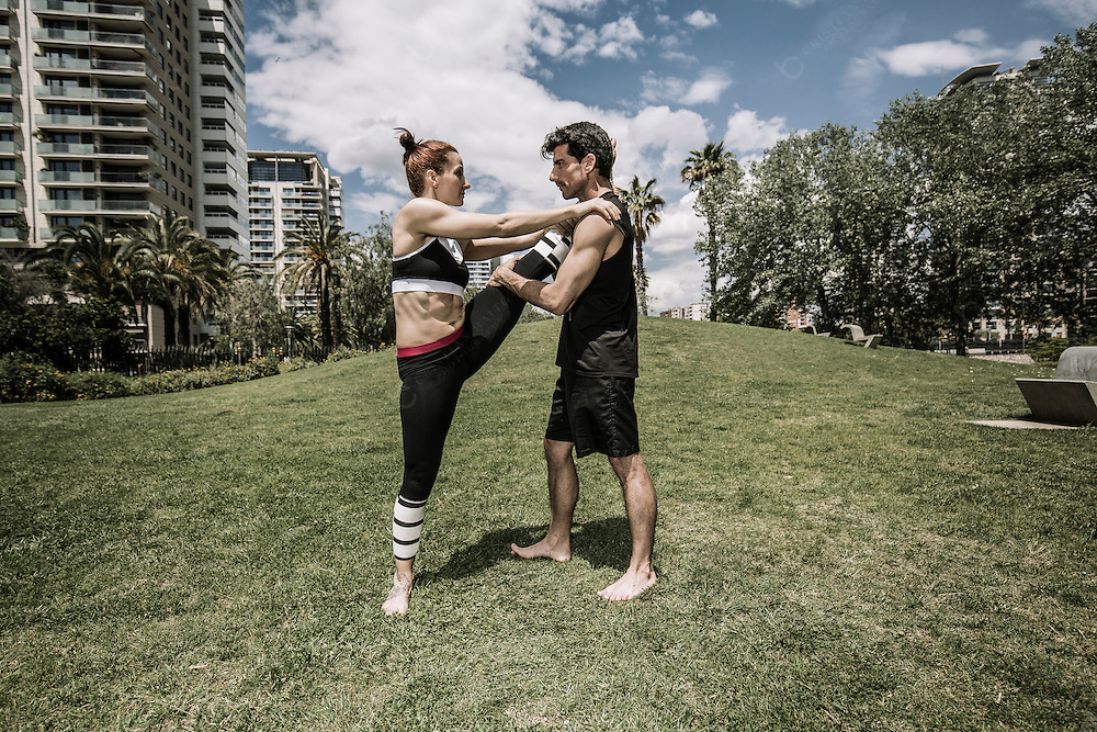 Man and woman doing stretching exercises in urban park