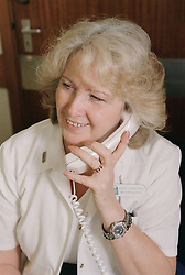 Medical ward receptionist talking on the telephone and smiling,