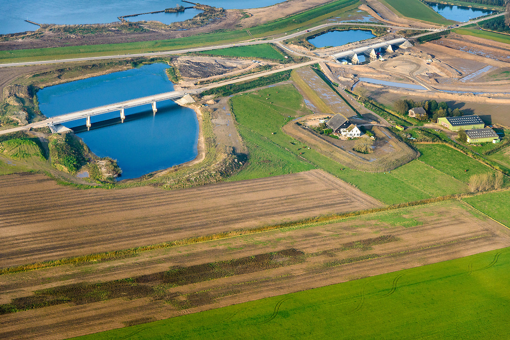 Nederland, Noord-Brabant, Werkendam, 28-10-2014; Ruimte voor de Rivier project Ontpoldering Noordwaard. Boven in beeld de Nieuwe Merwede, de bandijk is reeds voorzien van een doorlaat annex brug, rechts nieuwe terp voor (historische) boerderij.<br /> De Noordwaard wordt ontpolderd door de dijken aan de rivierzijde gedeeltelijk af te graven, hierdoor kan de Nieuwe Merwede bij hoogwater via de Noordwaard sneller naar zee stromen. Gevolg van de ingrepen is ook dat de waterstand verder stroomopwaarts zal dalen.<br /> National Project Ruimte voor de Rivier (Room for the River) By lowering and / or moving the dike of the Noordwaard polder the area will become subject to controlled inundation and function as a dedicated water detention district. Houses and farmhouses will be constructed on new dwelling mounds. <br /> luchtfoto (toeslag op standard tarieven);<br /> aerial photo (additional fee required);<br /> copyright foto/photo Siebe Swart