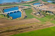 Nederland, Noord-Brabant, Werkendam, 28-10-2014; Ruimte voor de Rivier project Ontpoldering Noordwaard. Boven in beeld de Nieuwe Merwede, de bandijk is reeds voorzien van een doorlaat annex brug, rechts nieuwe terp voor (historische) boerderij.<br /> De Noordwaard wordt ontpolderd door de dijken aan de rivierzijde gedeeltelijk af te graven, hierdoor kan de Nieuwe Merwede bij hoogwater via de Noordwaard sneller naar zee stromen. Gevolg van de ingrepen is ook dat de waterstand verder stroomopwaarts zal dalen.<br /> National Project Ruimte voor de Rivier (Room for the River) By lowering and / or moving the dike of the Noordwaard polder the area will become subject to controlled inundation and function as a dedicated water detention district. Houses and farmhouses will be constructed on new dwelling mounds. <br /> luchtfoto (toeslag op standard tarieven);<br /> aerial photo (additional fee required);<br /> copyright foto/photo Siebe Swart