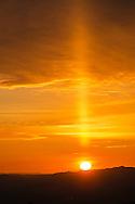 Sun Pillar and clouds at sunset over the Berkeley Hills, California