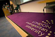 The purple corporate logo on lecture threatre carpet of London Metropolitan University's Holloway Road. A lecturer is seen in the distance, speaking to an unseen audience of students, hearing her talk about marketing and branding. London Metropolitan University is one of the foremost providers of undergraduate, postgraduate, professional and vocational education and training in Britain. Their courses are planned in consultation with employers and examining bodies in commerce, industry, the world of art and design, the financial services industries and other professions. To compare profiles, Oxford University has the lowest proportion of working-class students, with 11.5%. London Metropolitan University has the greatest proportion, with 57.2%. The first building, designed by Charles Bell, was opened in 1896.