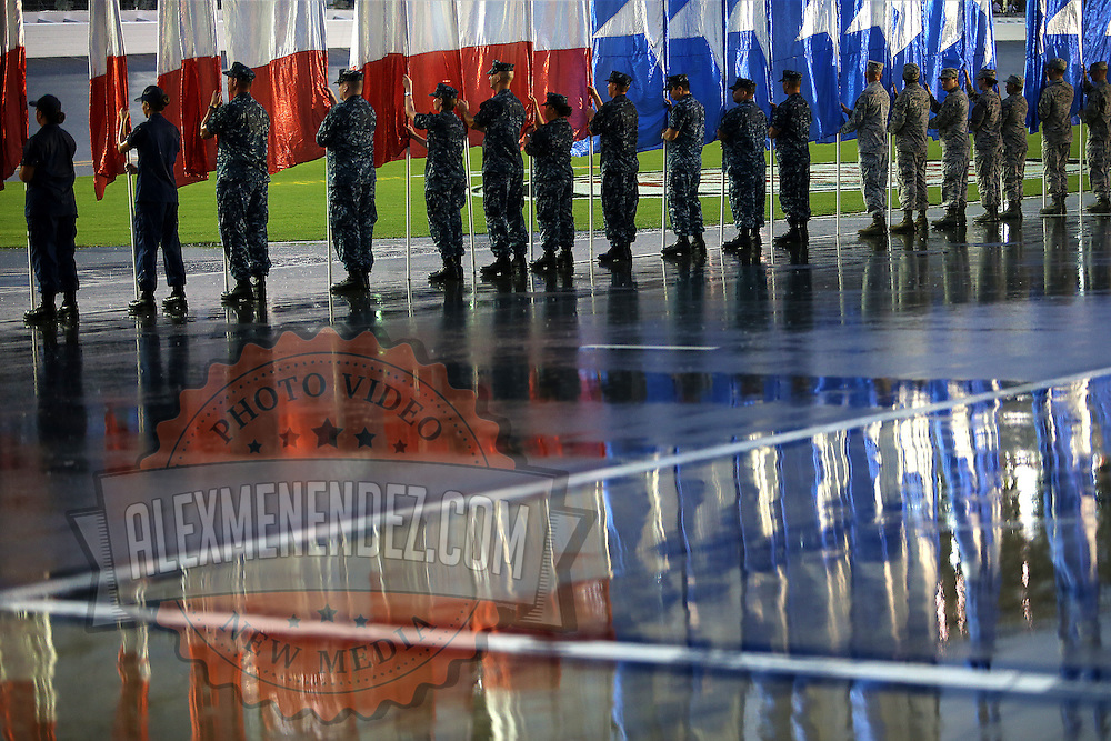 The Patrick Air Force Base Color Guard stands in the rain during the U.S. national anthem prior to the 57th Annual NASCAR Coke Zero 400 stock car race at Daytona International Speedway on Sunday, July 5, 2015 in Daytona Beach, Florida.  (AP Photo/Alex Menendez)