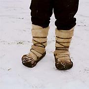 A Romanian peasant farmer wearing traditional footwear (opinci) worn with woollen felt foot wraps (obiele) at Ocna Sugatag market, Maramures, Romania
