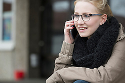 University student talking on mobile phone in campus School, Bavaria, Germany