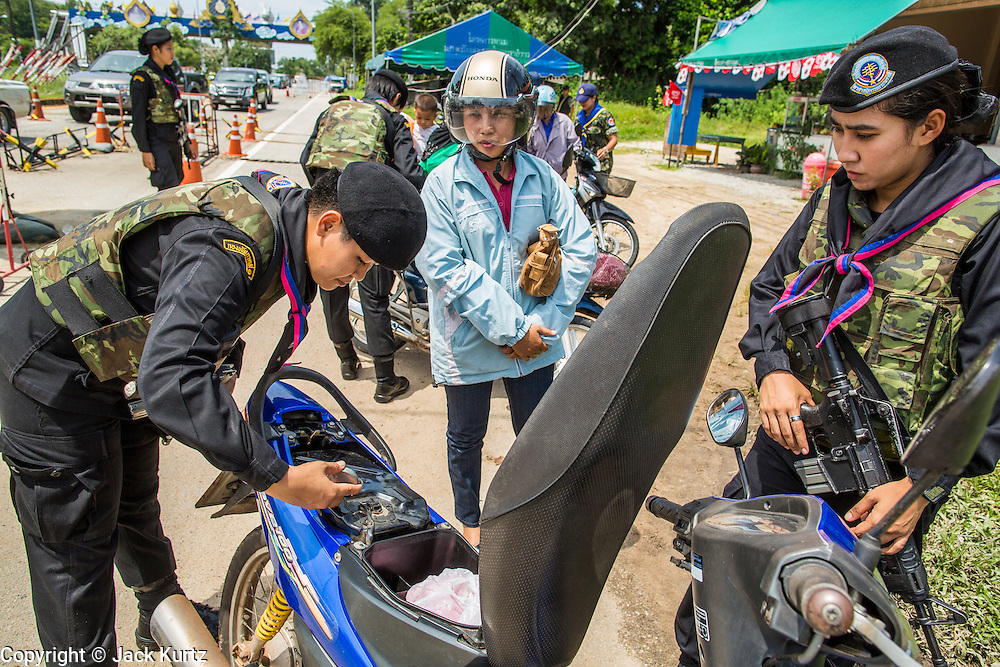"""25 OCTOBER 2012 - TAK BAI, NARATHIWAT, THAILAND: Thai women Rangers (paramilitary operating under Army command) check a woman's motorcycle at a checkpoint in Tak Bai, Thailand. The """"Tak Bai Incident"""" took place on Oct. 25 in Tak Bai, Narathiwat, Thailand during the Muslim insurgency in southern Thailand. On that day, a crowd gathered to protest the arrest of local residents. Police made hundreds of arrests during the protest and transported the arrested to Pattani, about two hours away, in another province. They were transported in locked trucks and more than 80 people suffocated en route. This enraged local Muslims and shocked people across Thailand. No one in the Thai army accepted responsibility for the deaths and no one was ever charged. In the past, the anniversary of the incident was marked by protests and bombings. This year it was quiet. More than 5,000 people have been killed and over 9,000 hurt in more than 11,000 incidents, or about 3.5 a day, in Thailand's three southernmost provinces and four districts of Songkhla since the insurgent violence erupted in January 2004, according to Deep South Watch, an independent research organization that monitors violence in Thailand's deep south region that borders Malaysia.   PHOTO BY JACK KURTZ"""