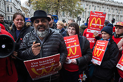 London, UK. 12 November, 2019. Asad Rehman, Executive Director of War On Want, addresses McDonald's workers belonging to the Bakers Food & Allied Workers Union (BFAWU) assembled opposite Downing Street during strike action, dubbed a 'McStrike', to call for a New Deal for McDonald's Workers which would include £15 an hour, an end to youth rates, the choice of guaranteed hours of up to 40 hours a week, notice of shifts four weeks in advance and union recognition.