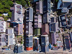 Aerial view from drone of tightly packed cottages in Seatown at historic village of Gardenstown on Moray firth Coast in Aberdeenshire, Scotland, Uk