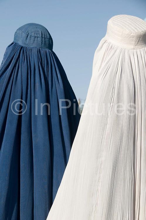 Mazar-e-Sharif, Afghanistan. Shrine to Hazrat Ali. Two women in burqas, one white, one blue.