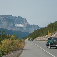 Vintage Model-T Fords drive on the Icefields Parkway in Banff National Park, Alberta, Canada.