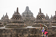 Indonesian tourists walk by the top platform of Borobudur temple in Central Java, Indonesia. The top platform of this monument has 72 perforated stupas with seated Buddha statues inside.