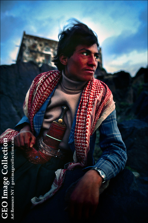 A bold-featured Yemeni shepherd sits on a rock outcropping wearing a traditional jambiya — in Arabic جنبية. A man's social status can often be discerned from these double-sided daggers., which are often made of illegally harvested African rhinoceros horn or ivory.