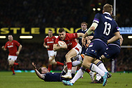 Gareth Davies of Wales © jumps over Scotland's Byron McGuigan as he breaks tow ards the try line.  Wales v Scotland, NatWest 6 nations 2018 championship match at the Principality Stadium in Cardiff , South Wales on Saturday 3rd February 2018.<br /> pic by Andrew Orchard, Andrew Orchard sports photography