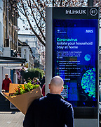 A BT InLinkUK digital sign displays NHS Coronavirus information as members of the public go about shopping for food and for mother's day and as the spring blossom comes out - Anti Coronavirus (Covid 19) outbreak in London.