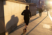 With most Londoners still working from home, a runner leaves his shadow on a wall of Royal Exchange while walking along a quiet Threadneedle Street during the evening rush-hour during the third lockdown of the Coronavirus in the City of London, the capital's financial district, on 26th February 2021, in London, England.
