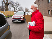 "06 APRIL 2020 - DES MOINES, IOWA: LARRY CLAUSON, puts a box of food into the back of a minivan during a drive through emergency food distribution at First DSM Church in Des Moines. Volunteers brought food to the people in the cars to maintain proper ""social distancing."" On Monday, 06 April, Iowa reported 946 confirmed cases of the Novel Coronavirus (SARS-CoV-2) and COVID-19. There have been 25 deaths attributed to COVID-19 in Iowa. Most non-essential businesses are closed until 30 April. Well over 100,000 Iowans filed first time claims for unemployment in the last three weeks, more than applied during the peak of the Great Recession of 2008. Local food banks have seen an equal spike in people seeking nutritional assistance. First DSM Church has increased their food pantry from one day weekly to three days per week. Hundreds of people lined up Monday to get a box of food and one roll of toilet paper at the church's drive through pantry.           PHOTO BY JACK KURTZ"