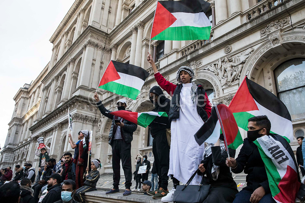 Palestinian flags are waved as thousands of people attend an emergency rally in solidarity with the Palestinian people organised outside Downing Street by Palestine Solidarity Campaign, Friends of Al Aqsa, Stop The War Coalition and Palestinian Forum in Britain on 11th May 2021 in London, United Kingdom. The rally took place in protest against Israeli air raids on Gaza, the deployment of Israeli forces against worshippers at the Al-Aqsa mosque during Ramadan and attempts to forcibly displace Palestinian families from the Sheikh Jarrah neighbourhood of East Jerusalem.