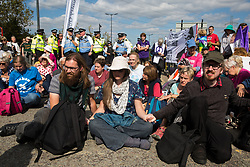 London, UK. 3 September, 2019. Metropolitan Police officers try to disperse hundreds of Quakers, joined by fellow peace activists and representatives of other faith groups, holding a religious service in the access road outside ExCel London as part of the day's No Faith In War activities in protest against DSEI, the world's largest arms fair.