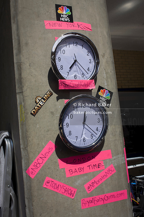 US NBC TV  time zone clocks in media village behind railings as tension mounts outside St Mary's Hospital, Paddington London, where media and royalists await news of Kate, Duchess of Cambridge's impending labour and birth. Some have been camping out for up to two weeks during a UK heatwave, having bagged the best locations where an heir to the British throne will eventually be shown to the world.