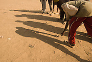 Children play marbles near the grass market, in the town of Abyei.