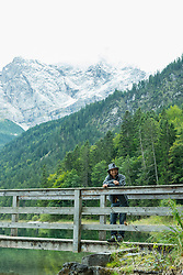 Tourist standing on pier at Eibsee lake, Bavaria, Germany