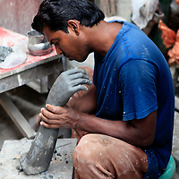 Asia, India, Calcutta. A clay sculptor from the potter's village of Kumartuli in Calcutta.