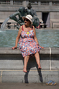 A woman wears a Union Jack flag pattern on her dress, after dipping her feet in chemically-treated fountain water in Trafalgar Square on Covid 'Freedom Day'. This date is what Prime Minister Boris Johnson's UK government has set as the end of strict Covid pandemic social distancing conditions with the end of mandatory face coverings in shops and public transport, on 19th July 2021, in London, England.