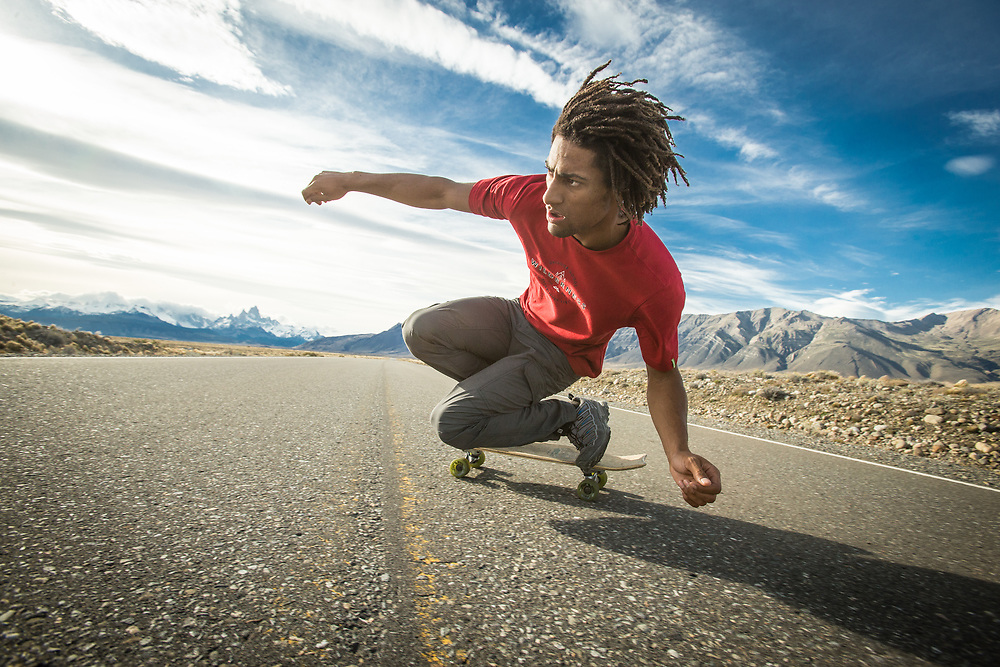 A skateboarder carving down the highway to El Chalten, Chile.